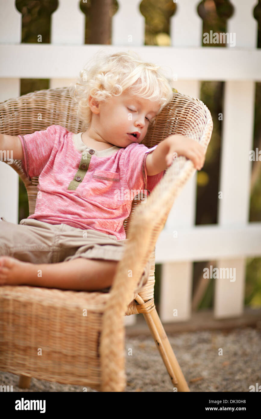 Blonde toddler boy with curly hair sleeping in wicker chair on patio - Stock Image