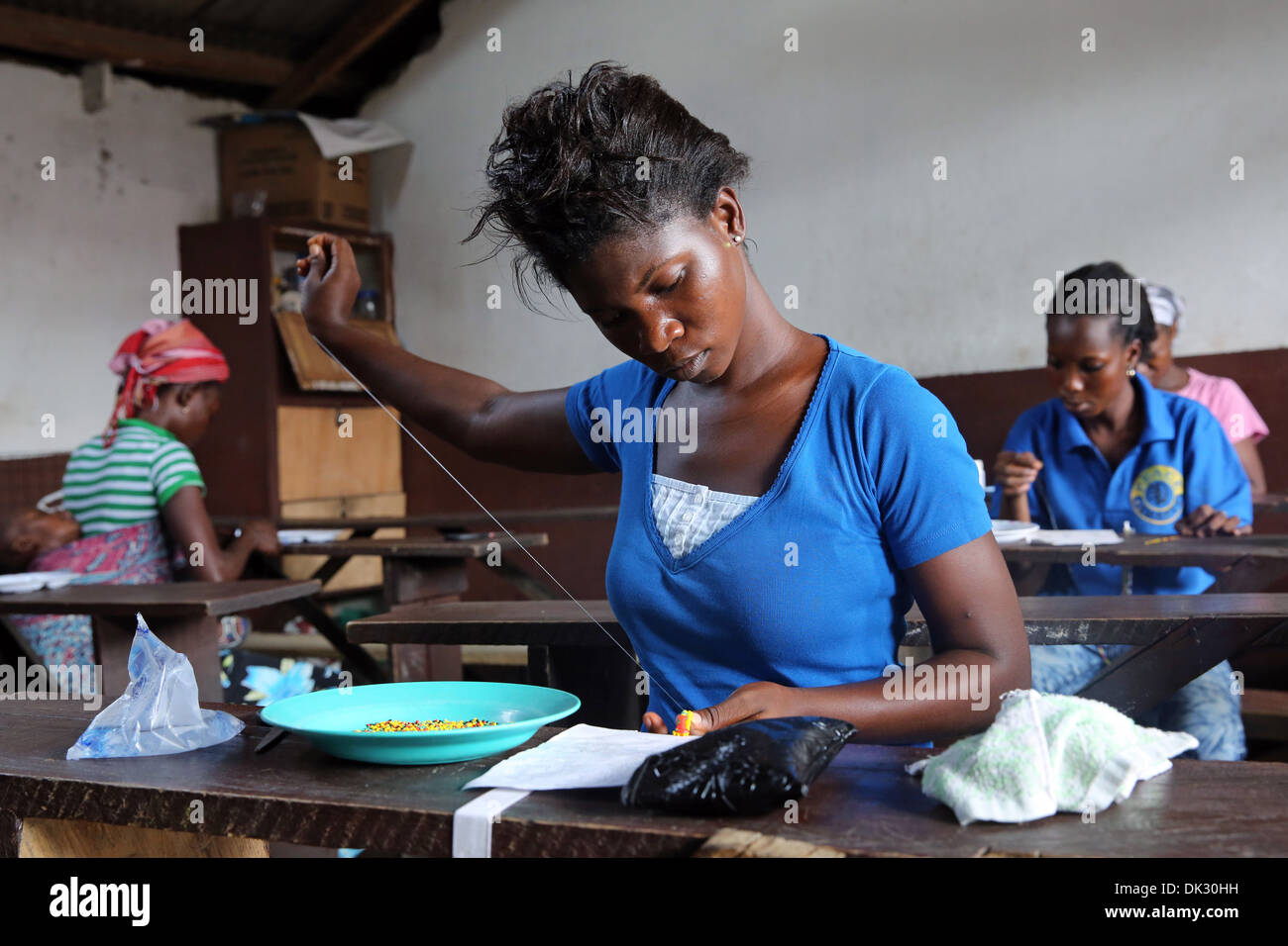 Women learning handcrafts in a voluntary day care center run by the catholic church. Township Agbogbloshie, Accra, West Africa - Stock Image
