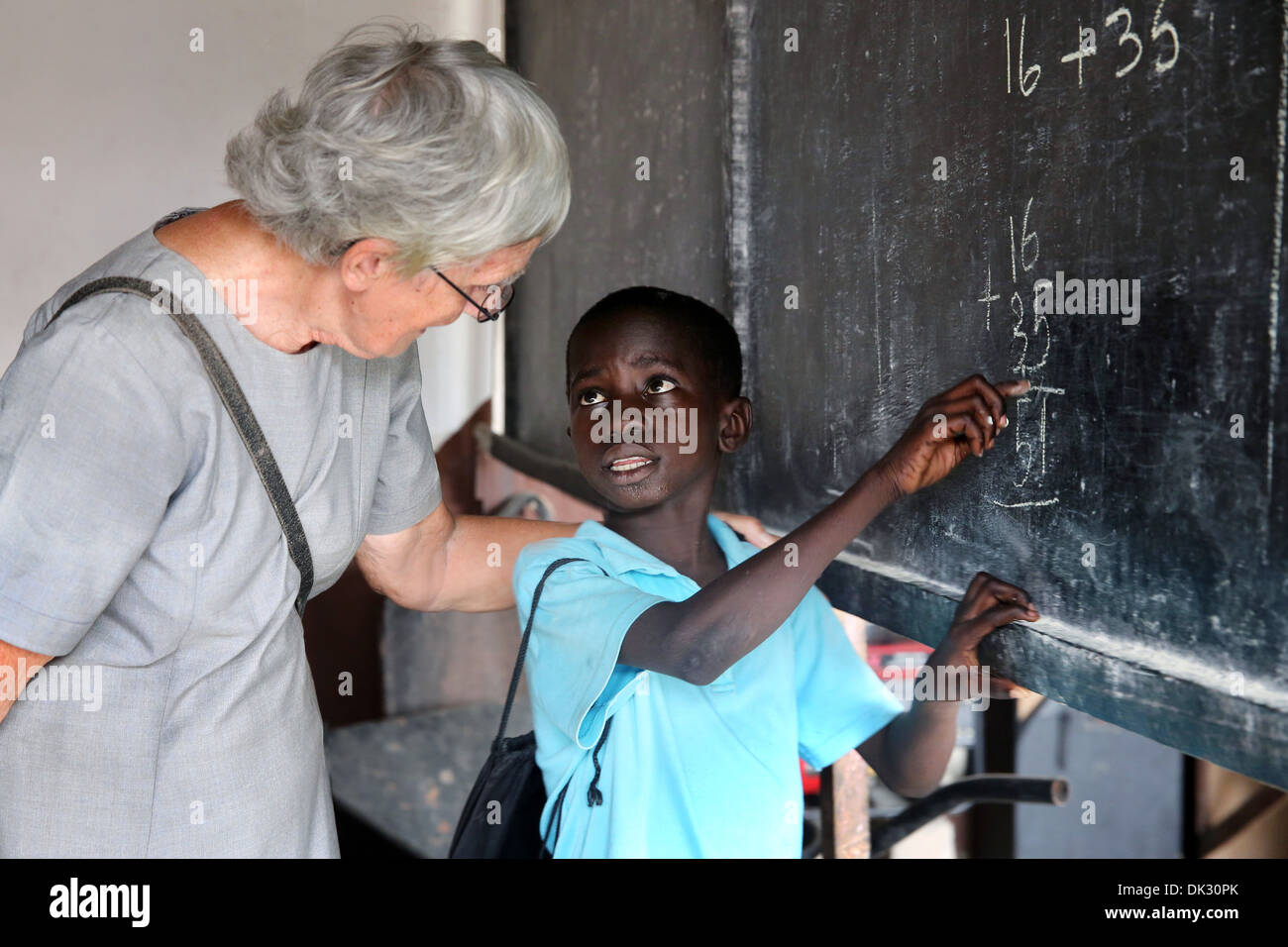 Black boy and white Teacher in a classroom of  a voluntary school run by the catholic church. Accra, West Africa - Stock Image