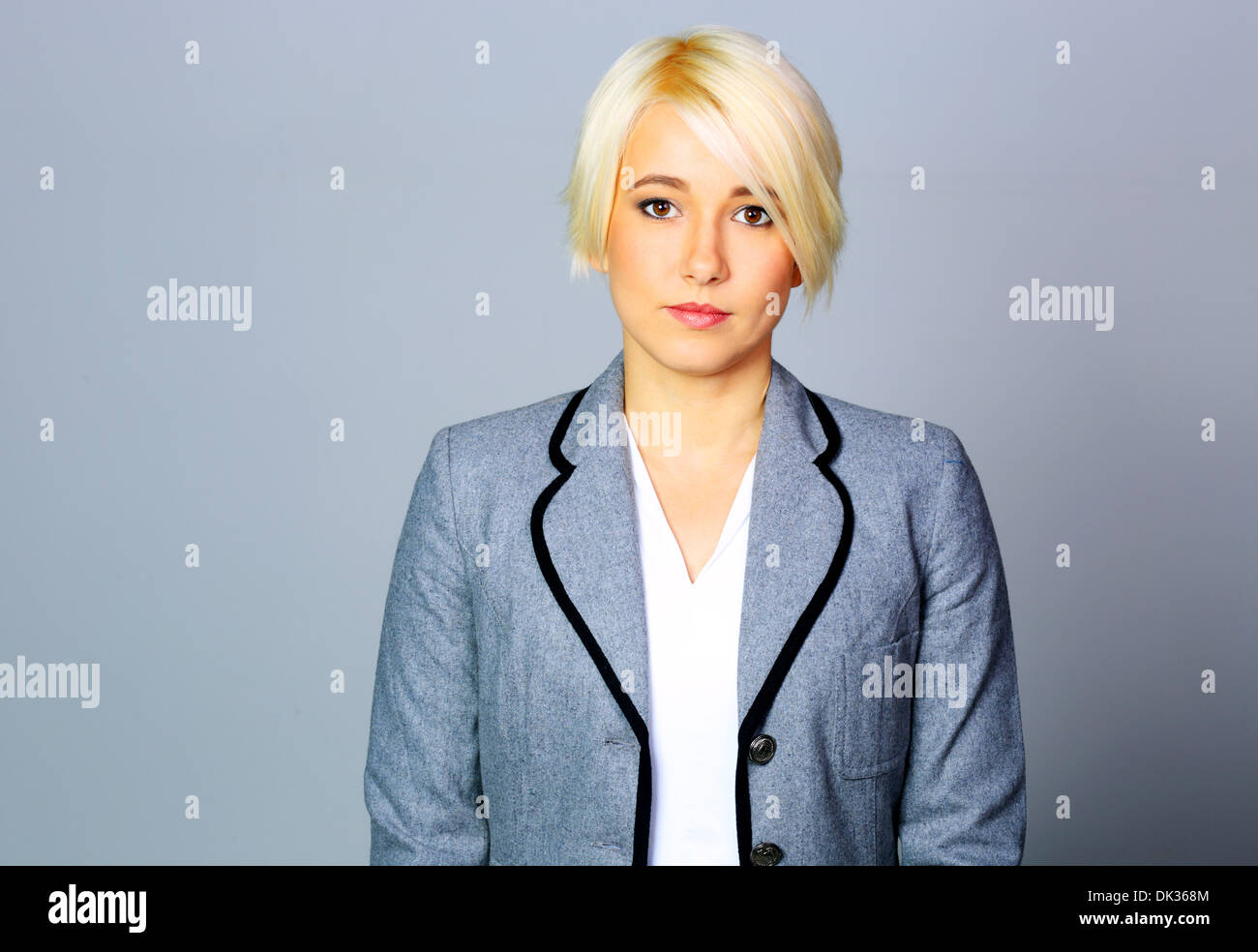 Thoughtfull businesswoman in gray jacket standing on gray background - Stock Image
