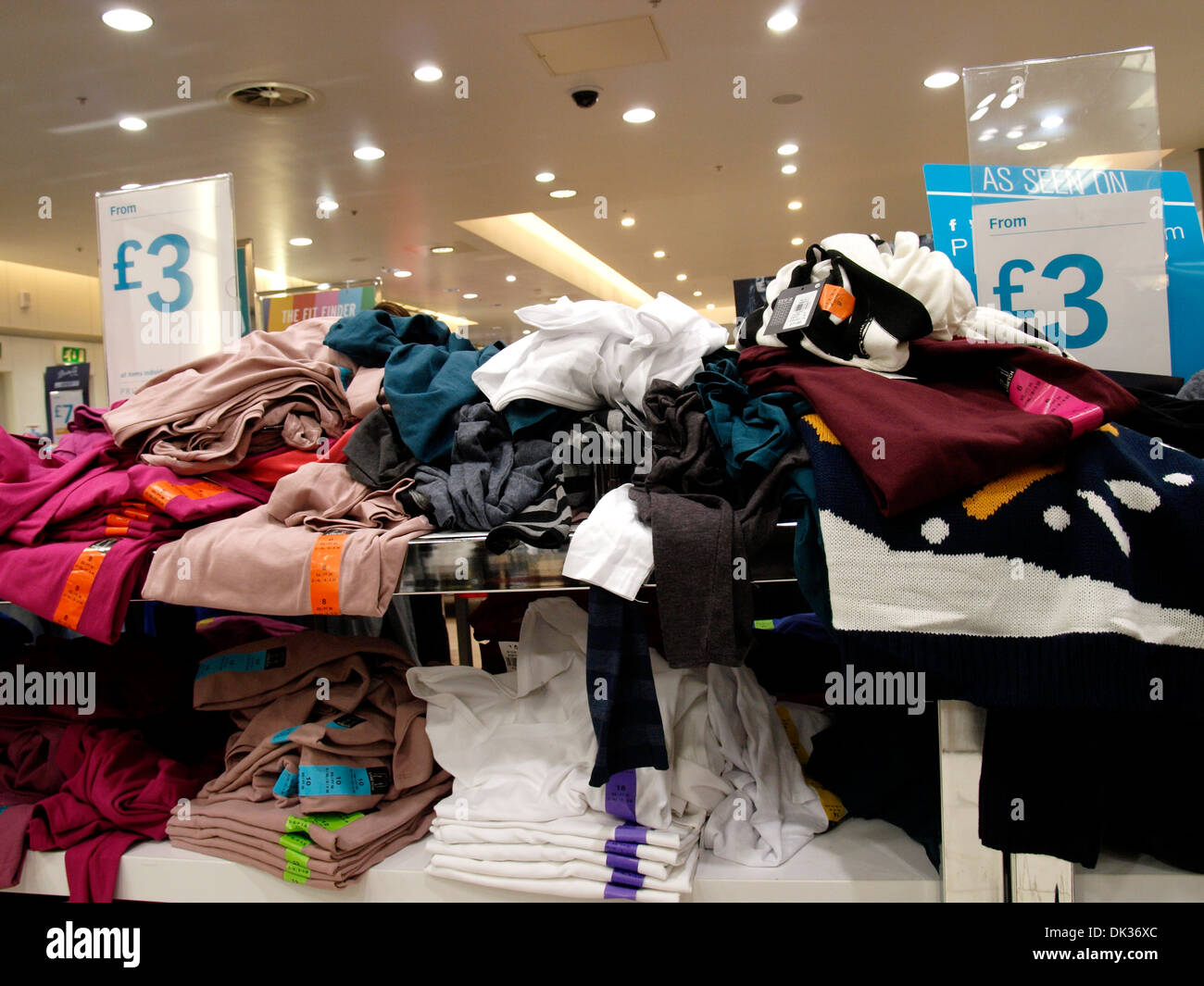 Shelves of cheap clothes for sale at Primark, Exeter, Devon, UK - Stock Image