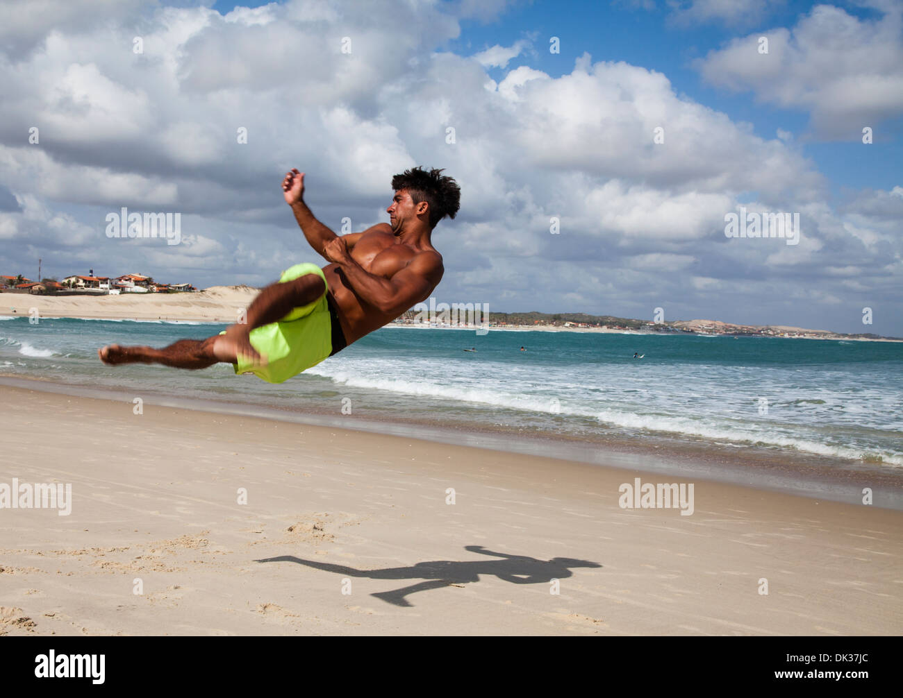 Man doing acrobatics on the beach in Iguape, Fortaleza district, Brazil. - Stock Image