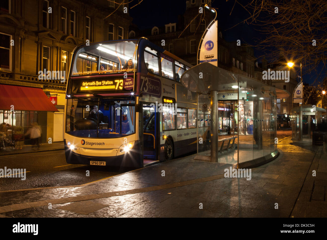 Rainy Night scene, Street lighting & Public Transport in the City of Dundee.  National Express Bus terminus in rain at dusk, Scotland, UK - Stock Image