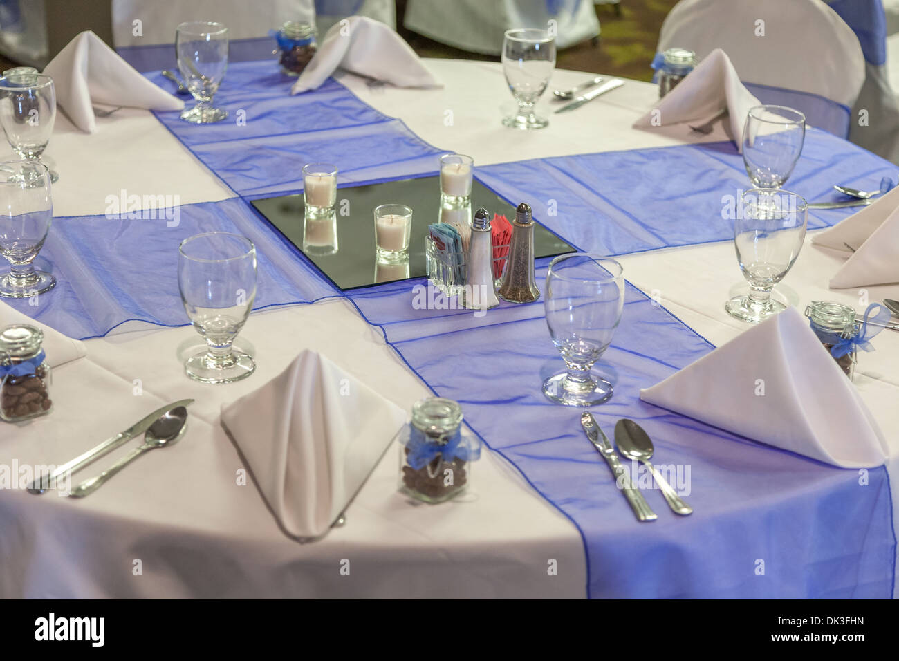 Formal table setting for wedding reception includes white table cloth and purple tulle accents & Formal table setting for wedding reception includes white table ...