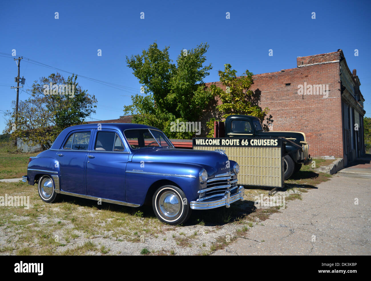 1948 Plymouth Special De Luxe parked by a 'Welcome Route 66 Cruisers' sign and a 40s Ford truck in Galena, Kansas - Stock Image