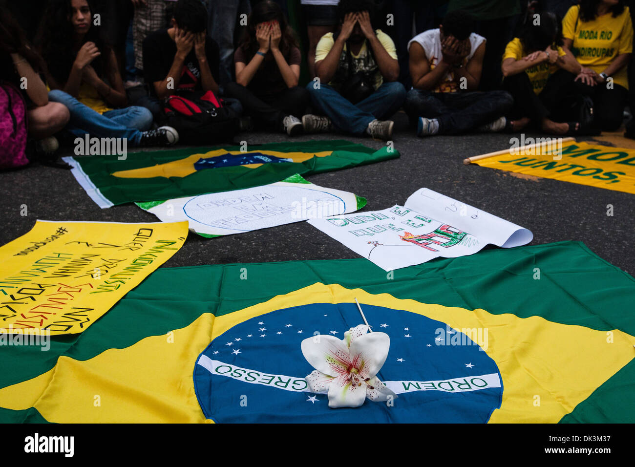 Brazil 2013 protests Young people cover their faces in shame for corruption in Brazilian Government, Brazil flag and flower - Stock Image