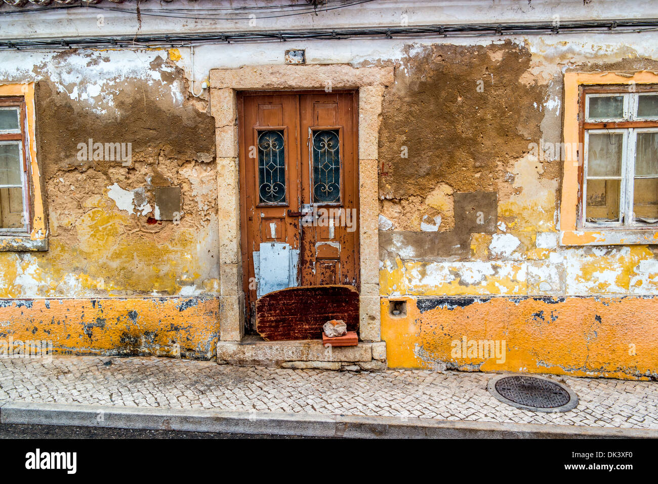 Old building in a state of dilapidation with paint and cement peeling off the walls - Stock Image