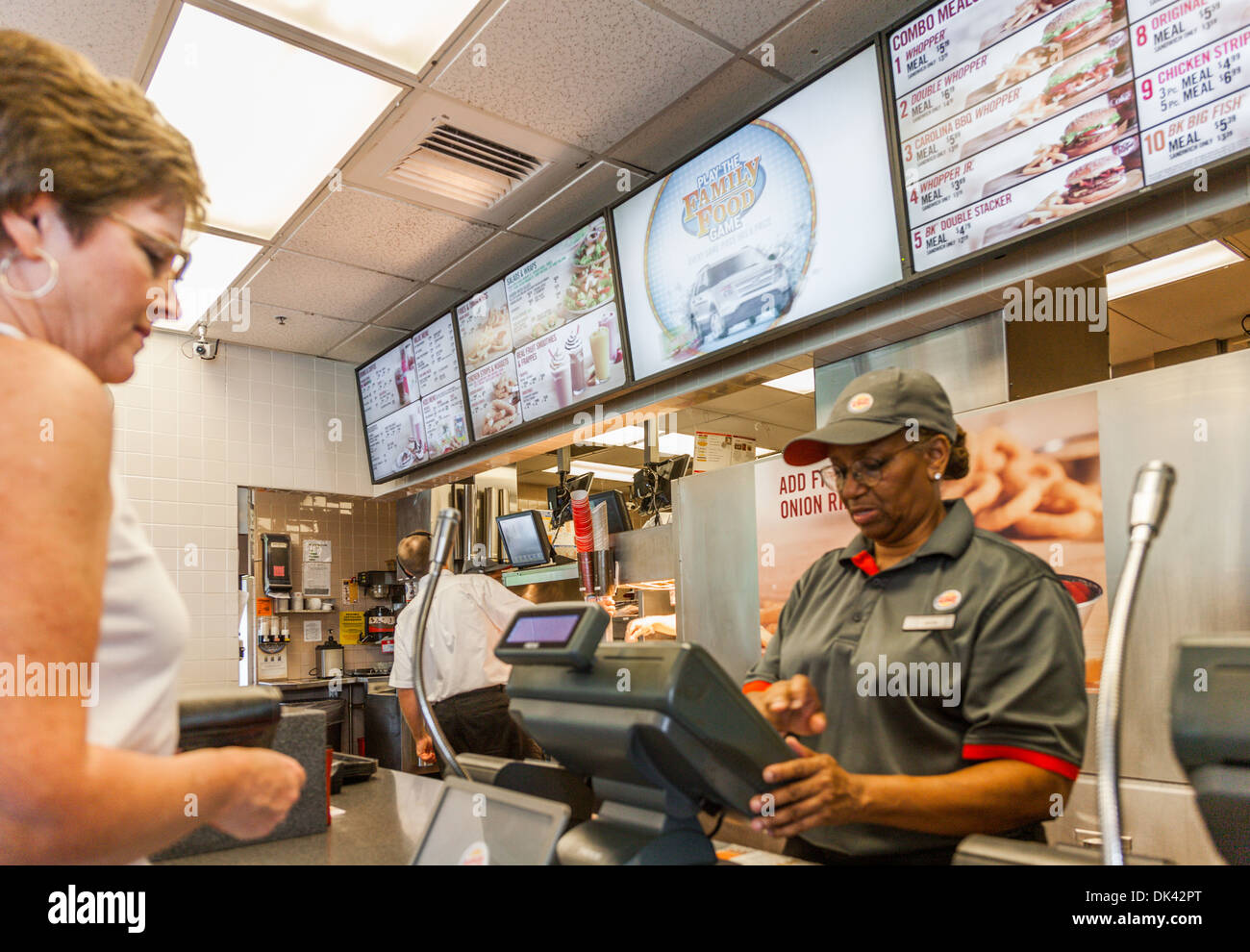 Female customer ordering fast food in a Burger King restaurant - Stock Image
