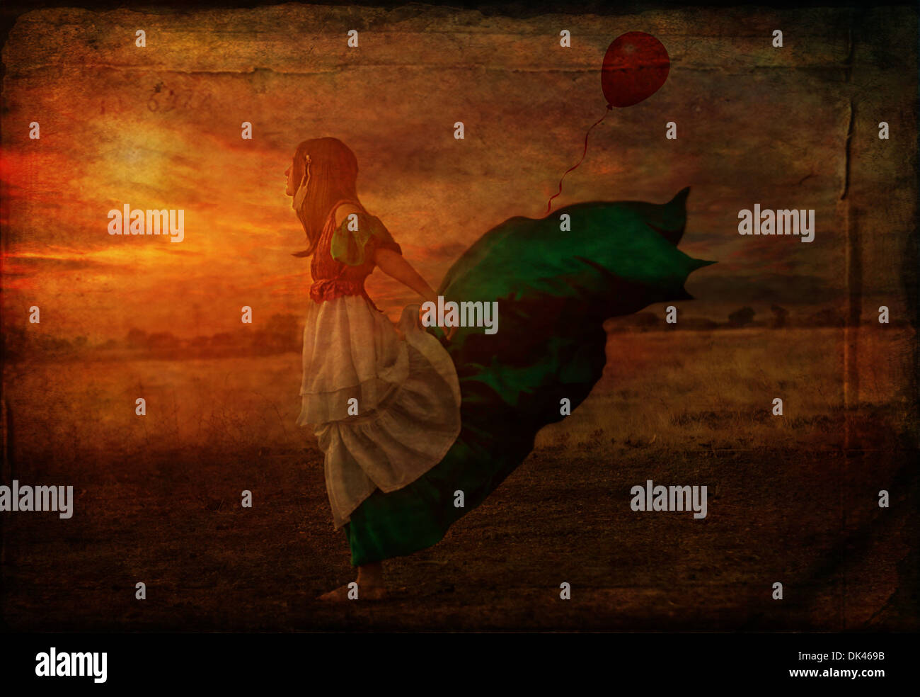 Girl with red balloon long dress blowing in the wind - Stock Image