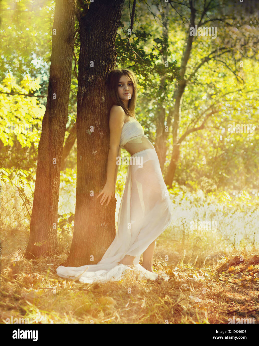 Young girl leaning on tree - Stock Image