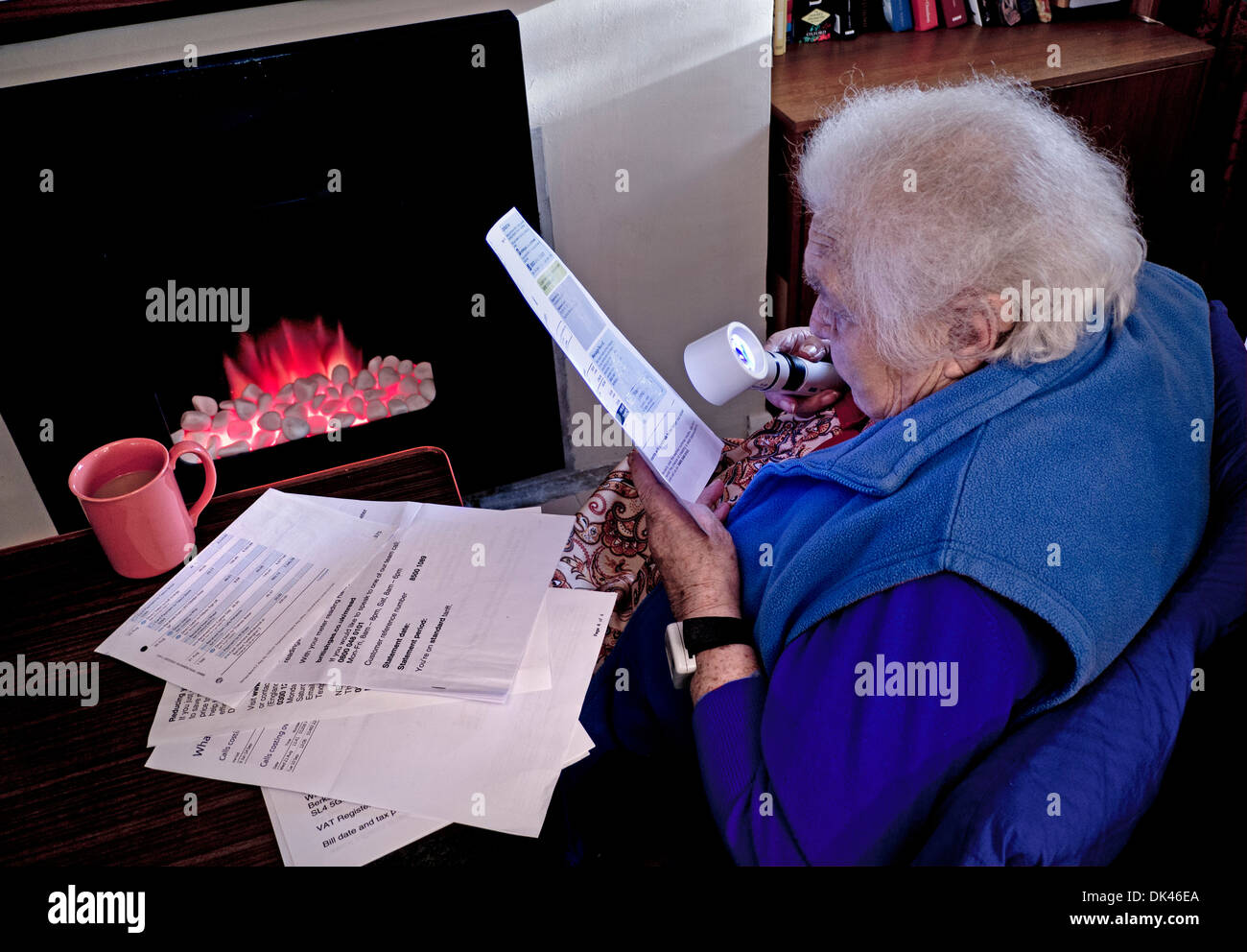 WINTER HEATING BILLS Elderly senior independent 99 year old lady at home in front of fire using a magnifier to read her winter household energy bills - Stock Image