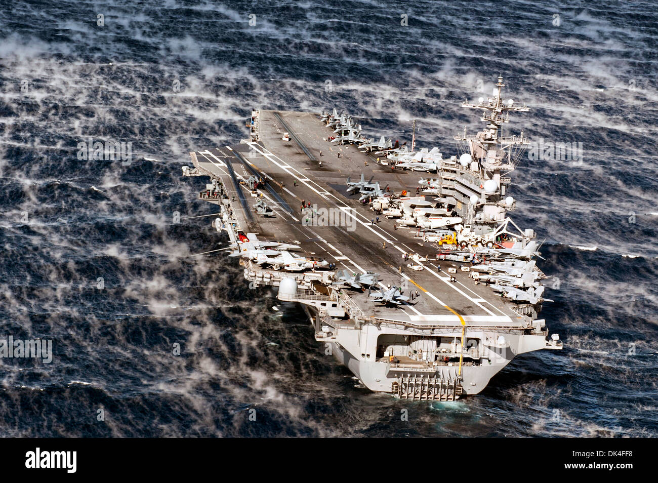 US Navy nuclear powered aircraft carrier USS George H.W. Bush steams through stormy seas during training exercises November 24, 2013 in the Atlantic Ocean. - Stock Image