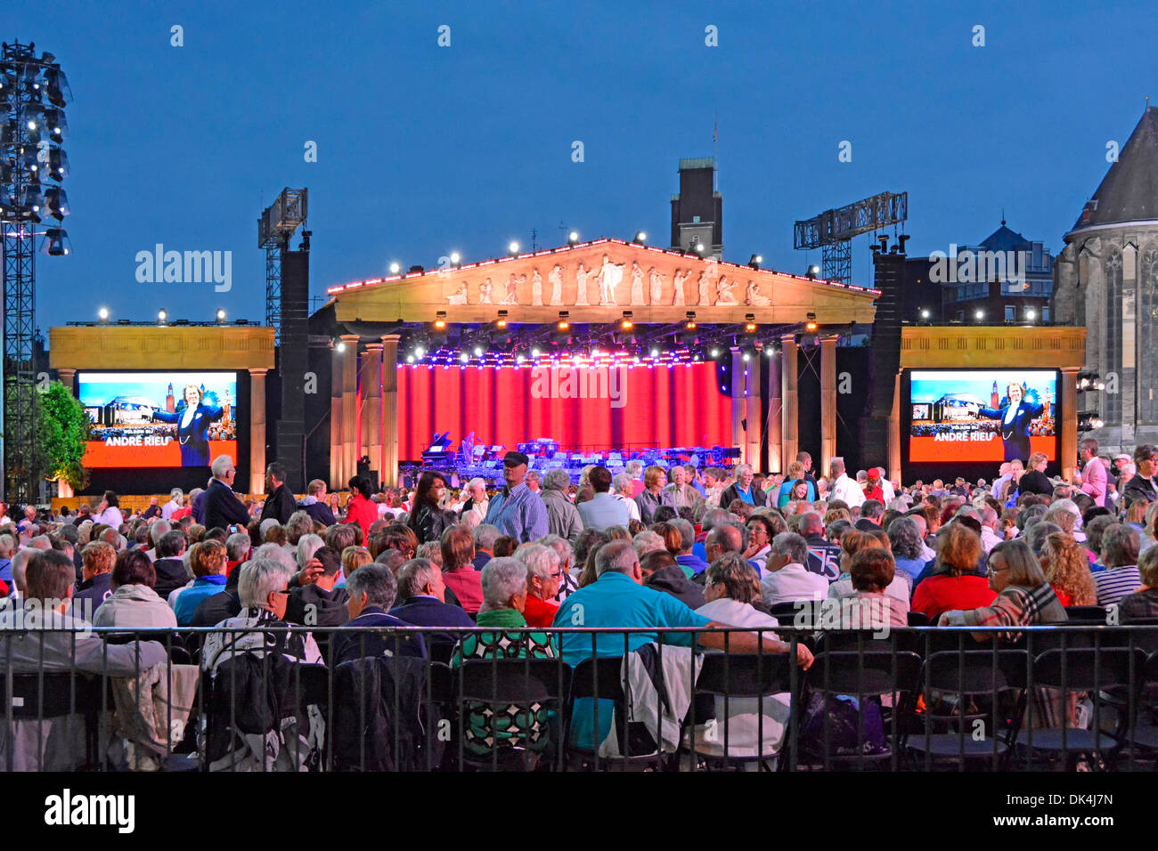 Audience in Vrijthof Square during interval for a André Rieu summer evening music concert showing stage & large TV screens - Stock Image