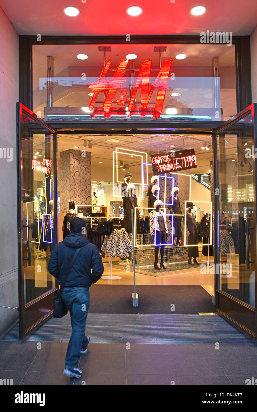 Customer entering H&M  clothing store with interior fashion displays beyond - Stock Image