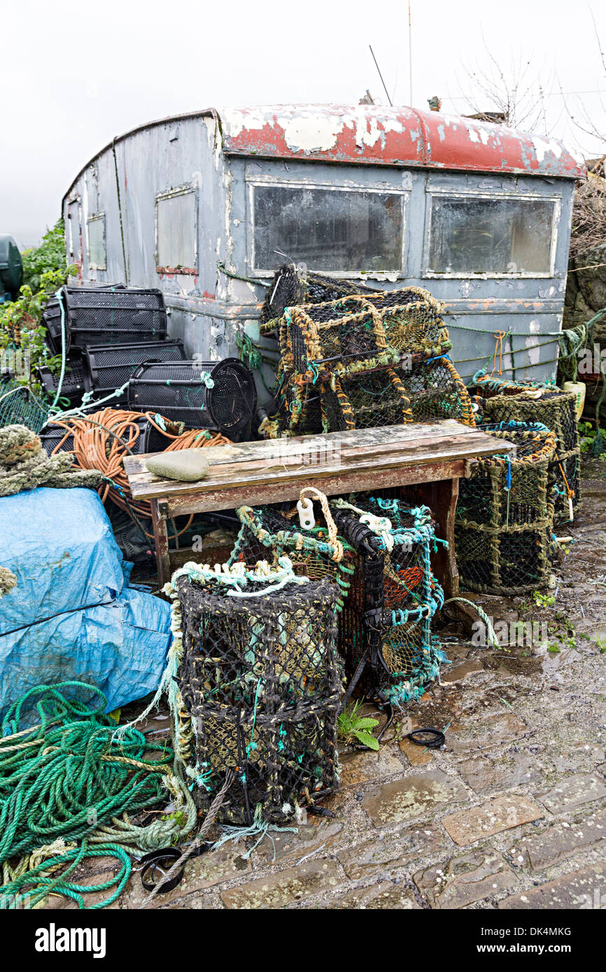Old lobster pots and caravan on quay, Liscannor, Co. Clare, Ireland - Stock Image