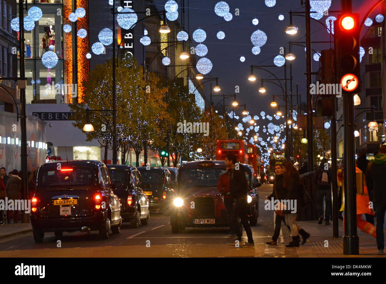 Oxford Street Christmas decorations with taxis and pedestrians - Stock Image