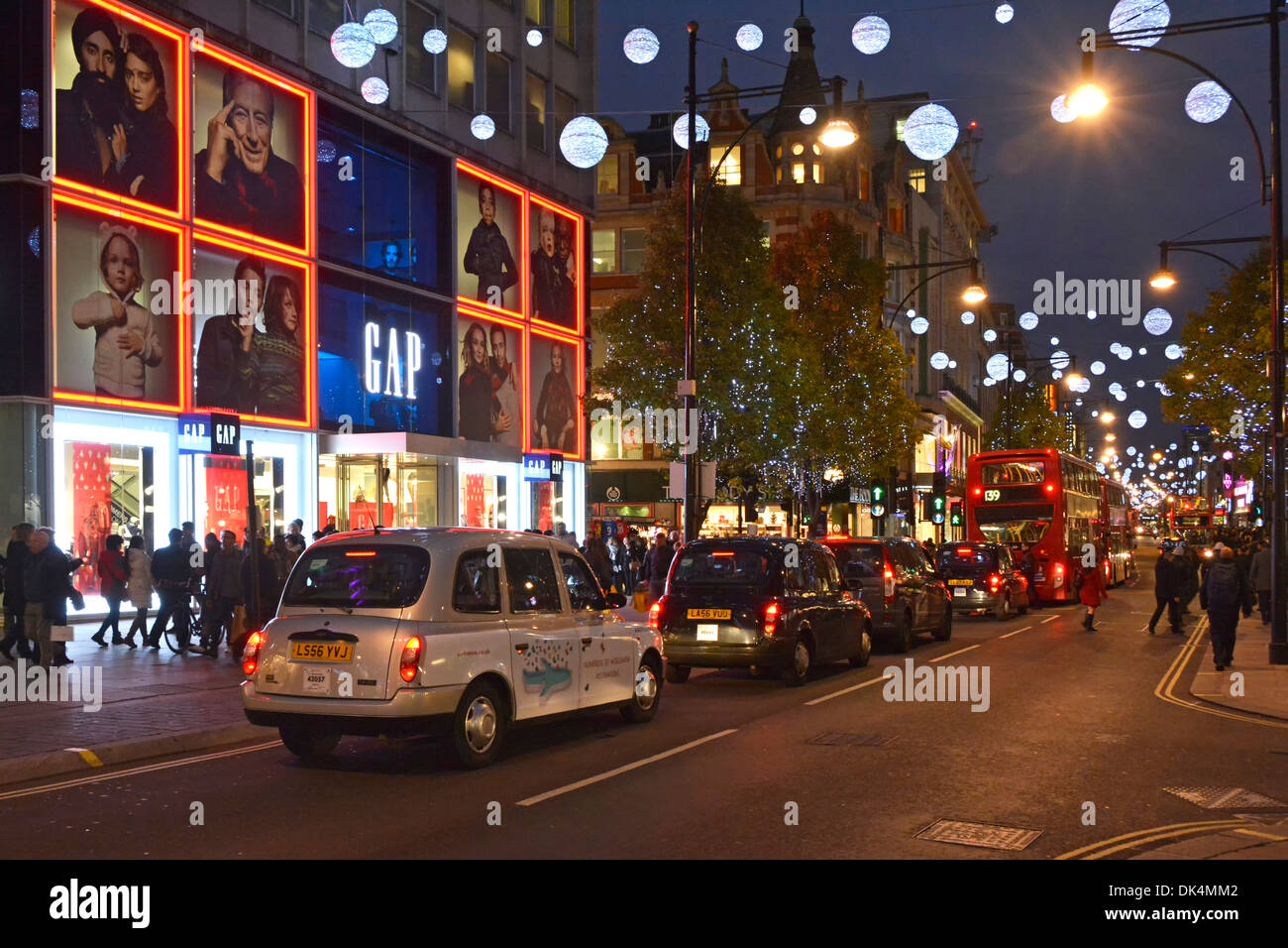 London taxis and buses queuing in Oxford Street  below Christmas decorations - Stock Image