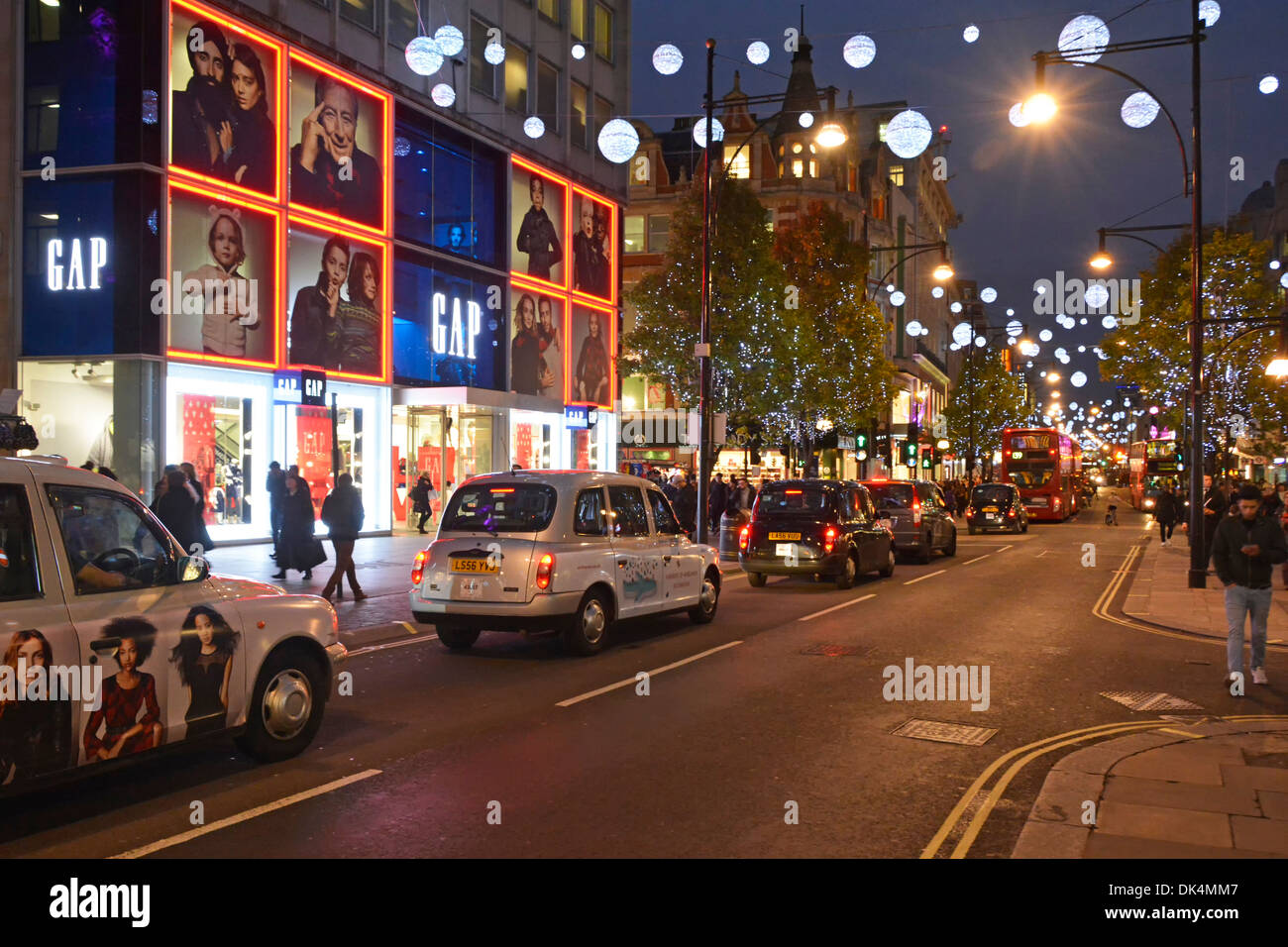 London taxis queuing in Oxford Street below Christmas decorations - Stock Image