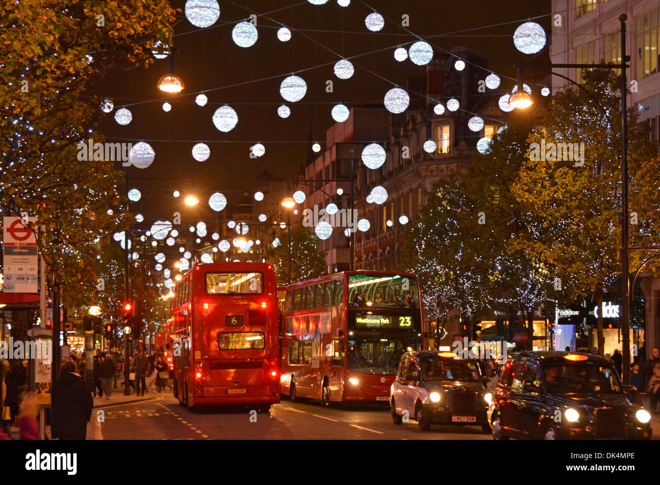 London taxis and buses in Oxford Street  below Christmas decorations - Stock Image