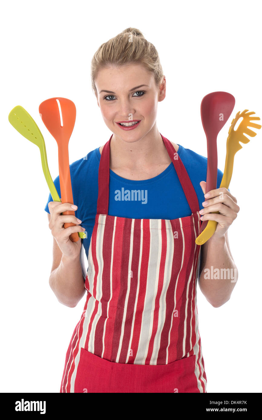 Model Released. Attractive Young Woman Holding Cooking Utensils - Stock Image