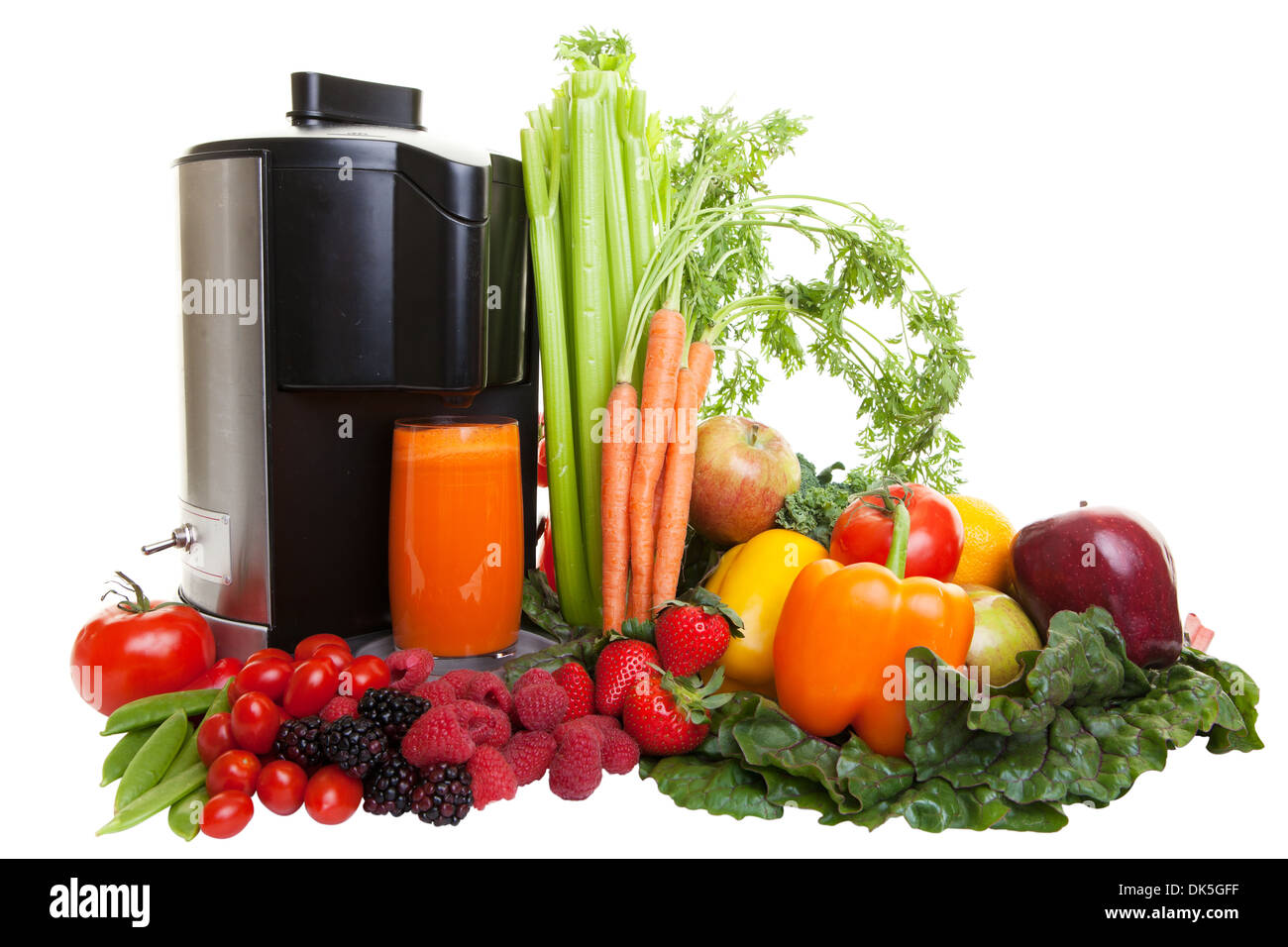 A Juicer surrounded by healthy fruits and vegetables, isolated on white. - Stock Image