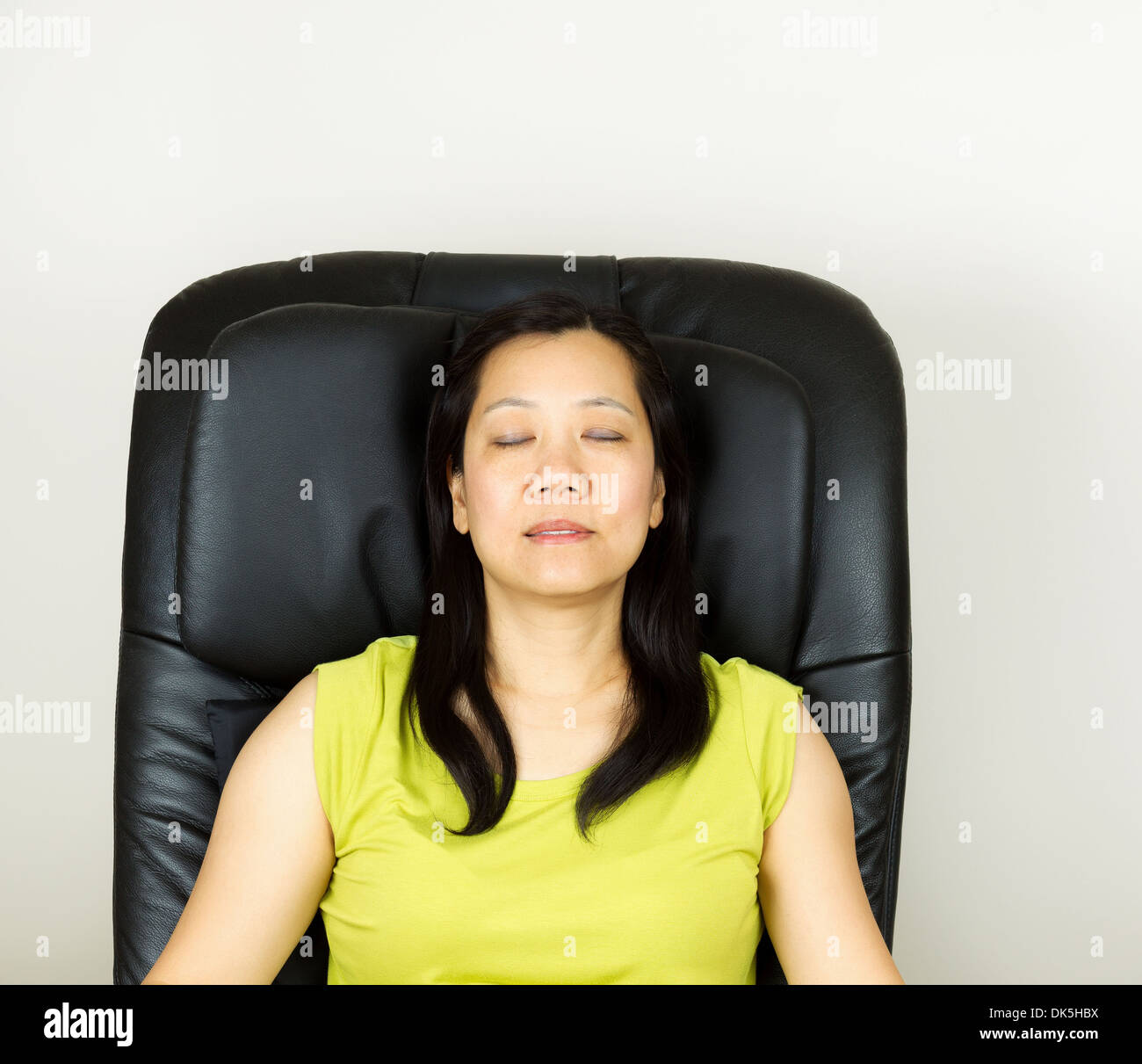 Photo Of Mature Woman Relaxing In Massage Chair Eyes Closed With Wall In Background