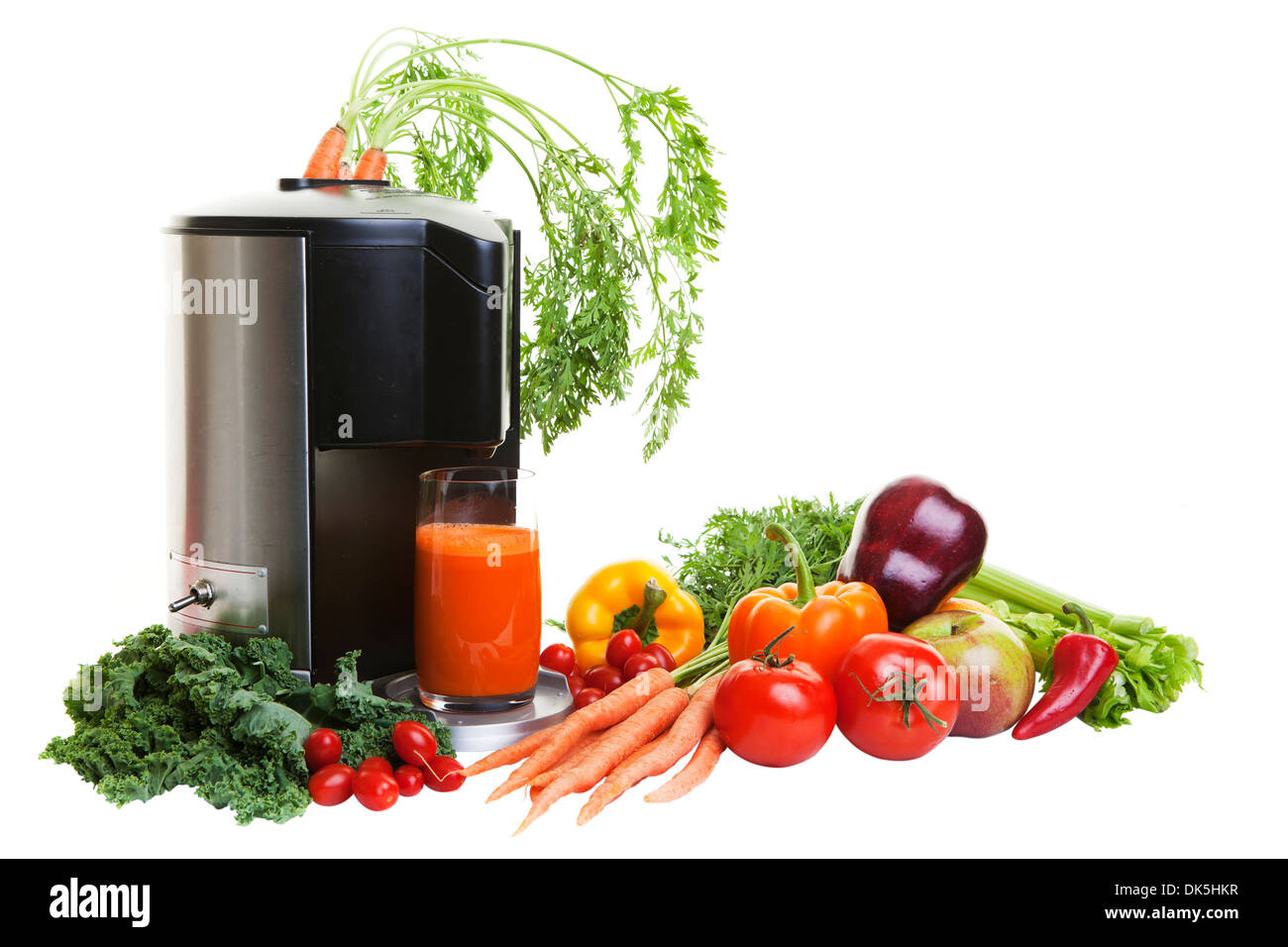 A Juicer surrounded by healthy vegetables and fruit, isolated on white. - Stock Image
