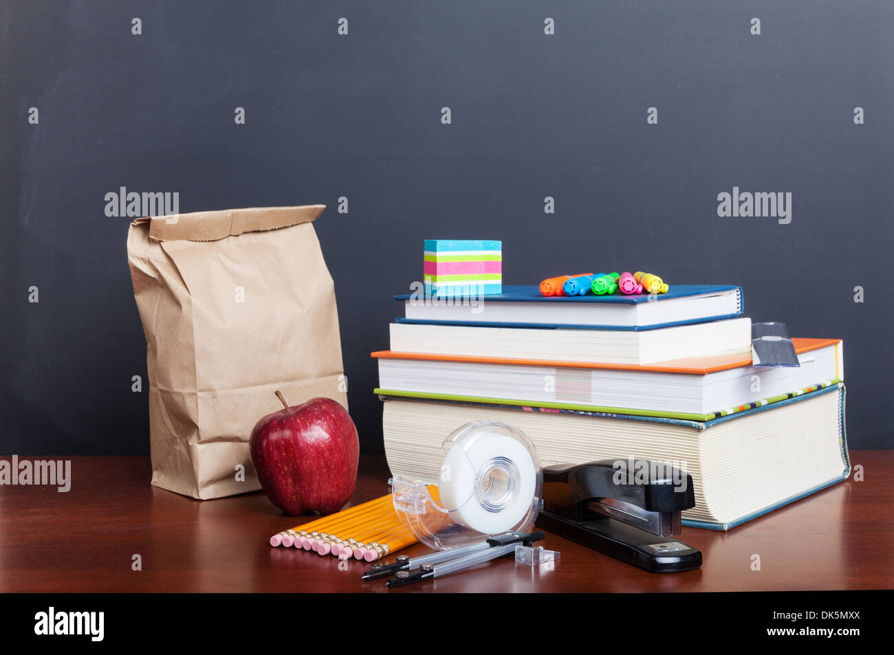 School books with apple and paper bag lunch on desk in front of a blank chalkboard. - Stock Image