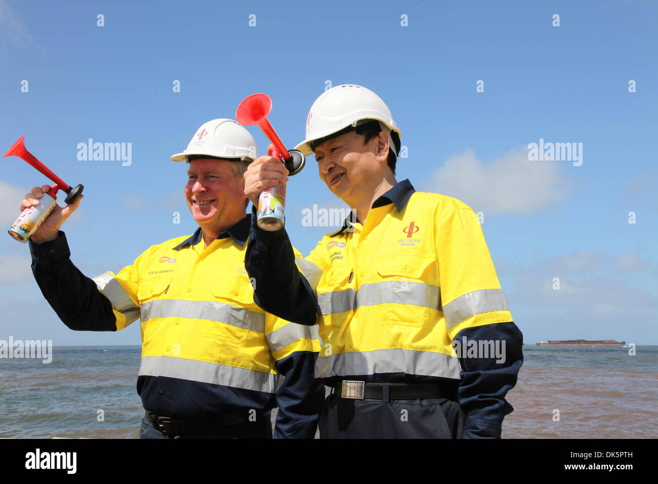 (131203) -- PORT CAPE PRESTON, Dec. 3, 2013 (Xinhua) -- Premier of Western Australia Colin Barnett (L) and Chang Zhenming, chairman of CITIC Group, beep horns as a barge loaded with magnetite concentrate of CITIC Pacific Mining leaving Port Cape Preston, Western Australia, December 2, 2013. The first shipment of magnetite concentrate by CITIC Pacific Mining departed Port Cape Preston, Western Australia, on Monday, an encouraging move for the troubled project. The project, China's largest overseas investment in the resources sector, has become a cash black hole due to ballooning costs and delay - Stock Image