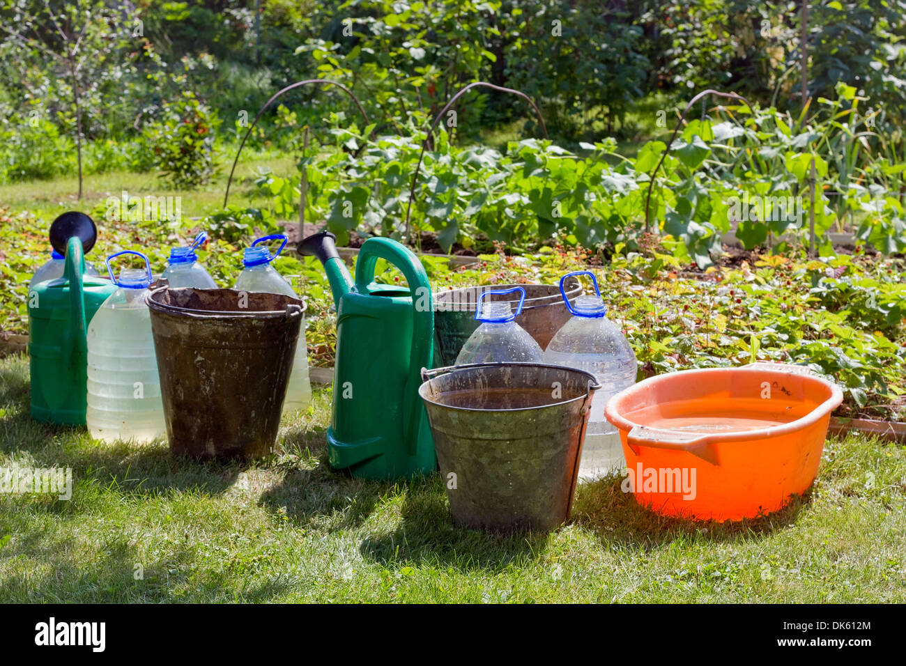 Thirst concept. Hot sunny summer day and the water in buckets and cans. Soft art focus - Stock Image