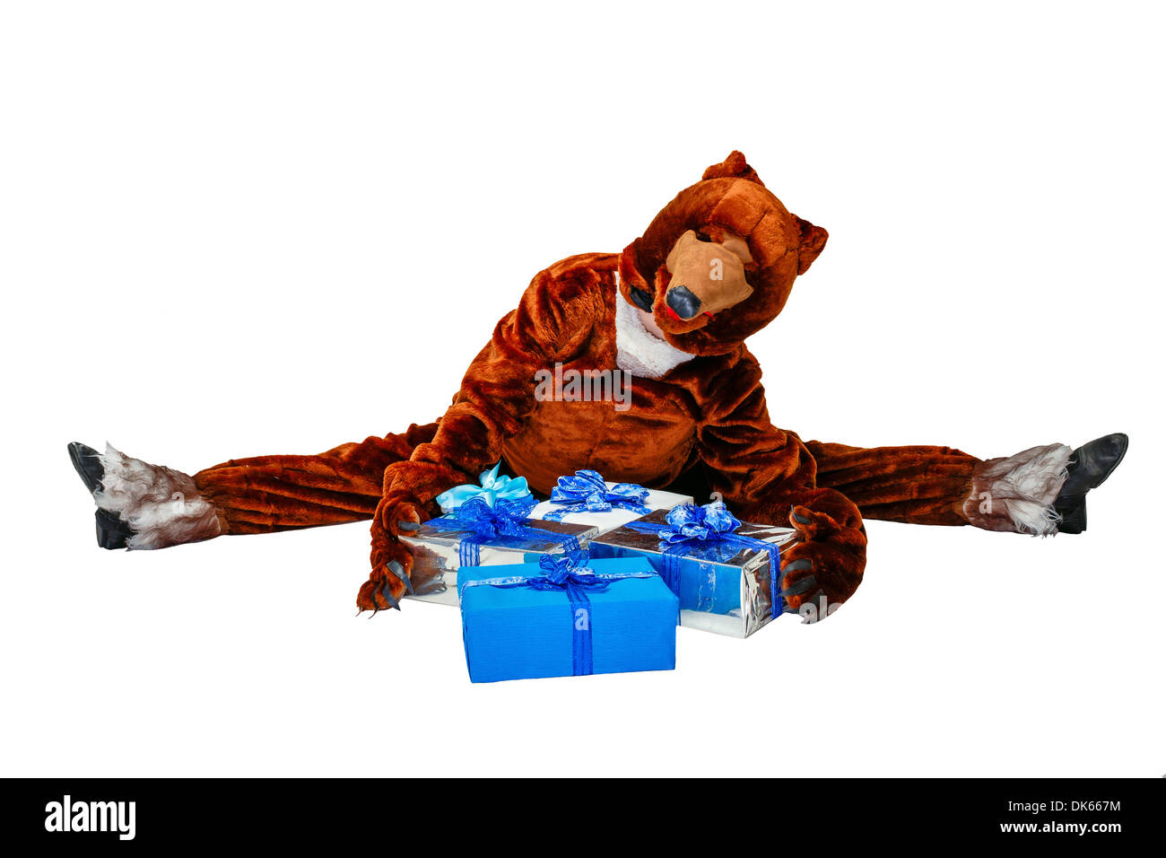 Girl in a bear costume holding Christmas gifts isolated on white background - Stock Image