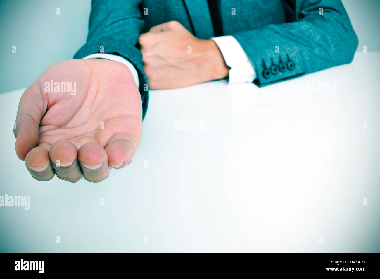 man wearing a suit sitting in a table with an outstretched hand Stock Photo