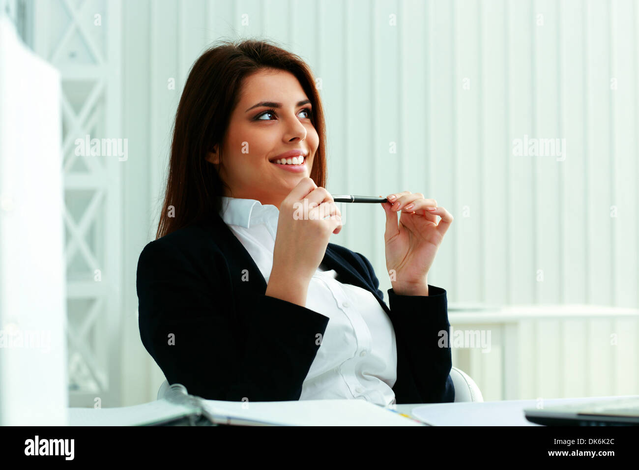 Young smiling businesswoman sitting at the table and looking away at copyspace in office - Stock Image