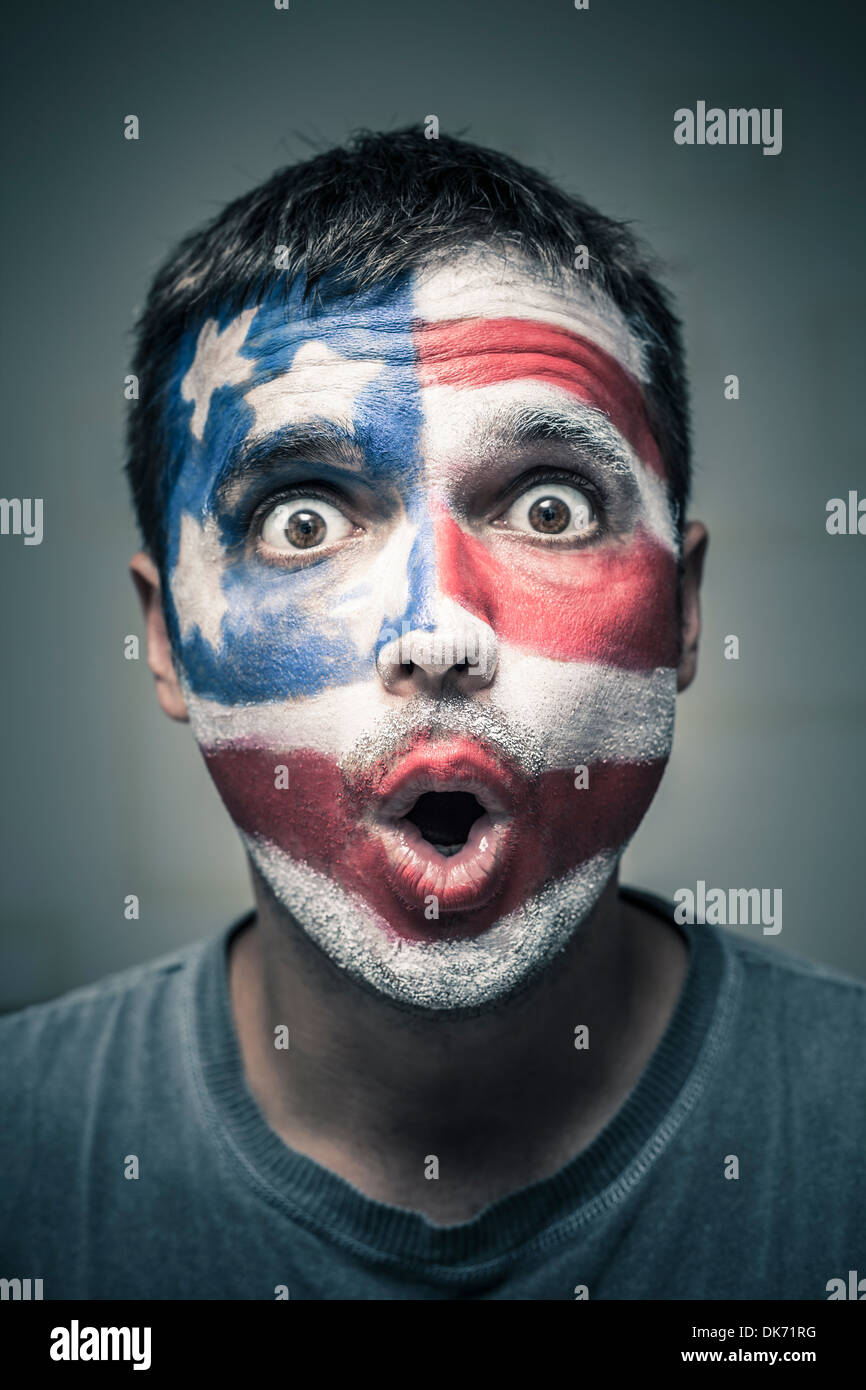 Portrait of surprised man with US flag painted on face. - Stock Image