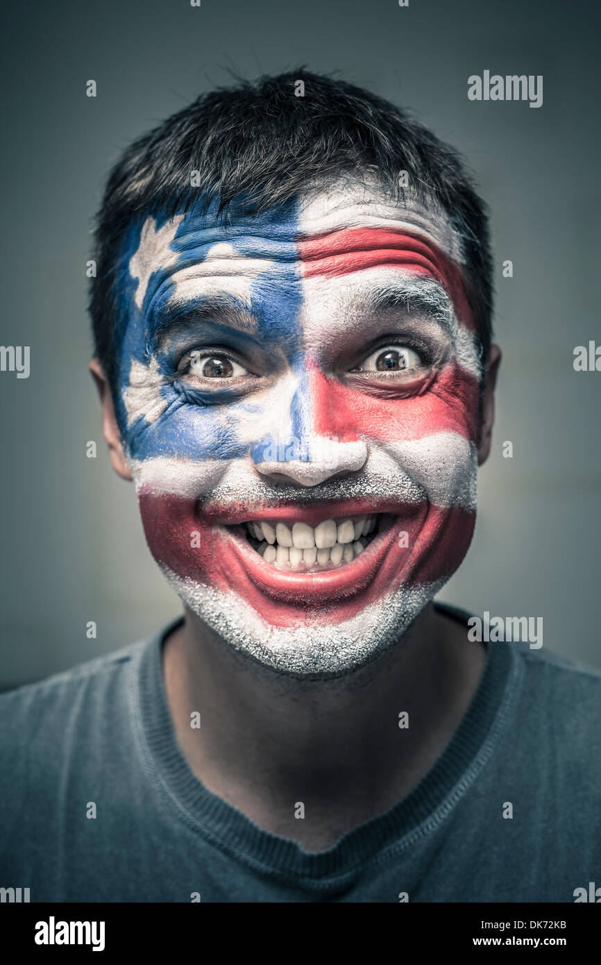 Portrait of funny toothy smiling man with US flag painted on face. - Stock Image