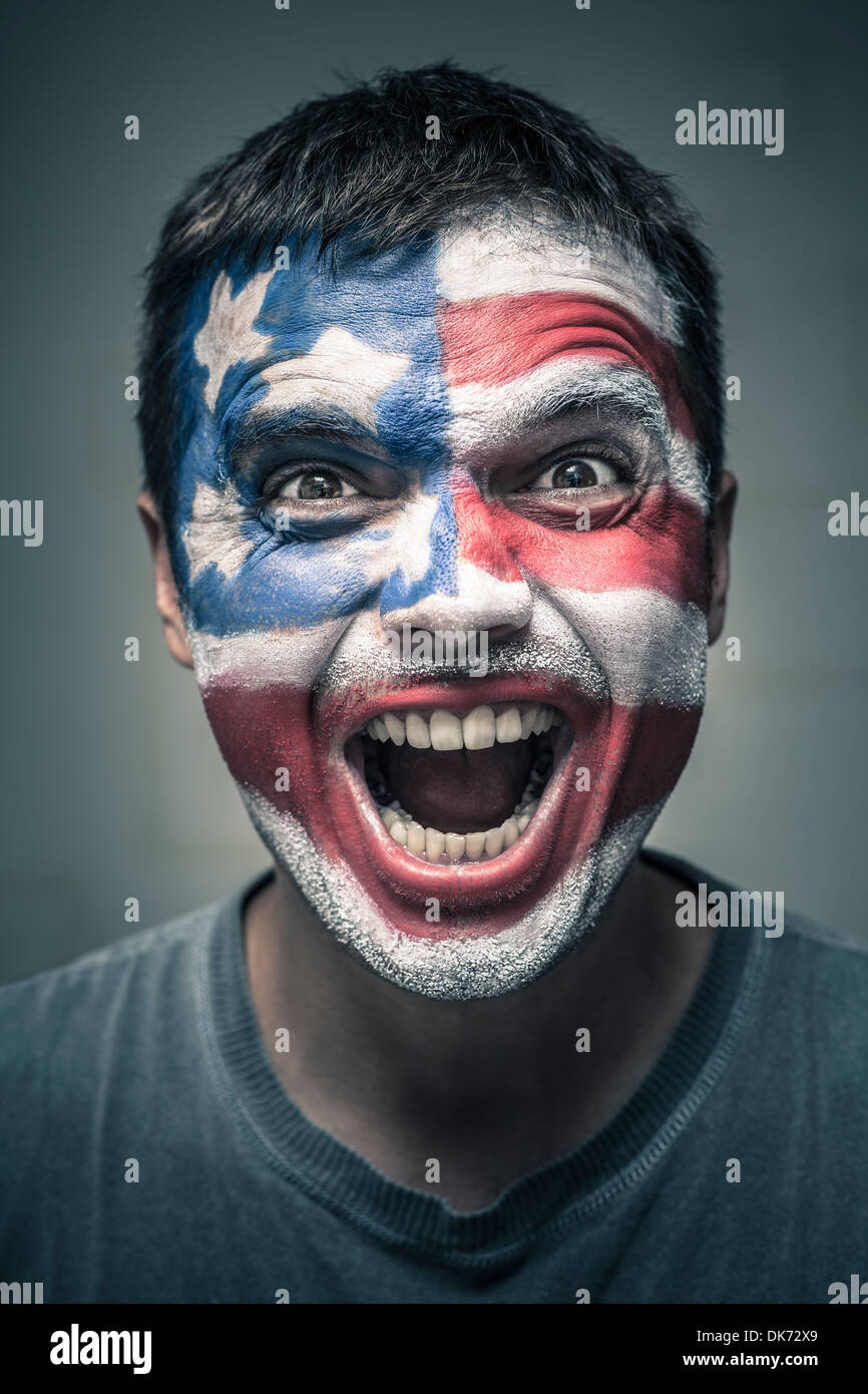 Portrait of exited man with US flag painted on face. - Stock Image