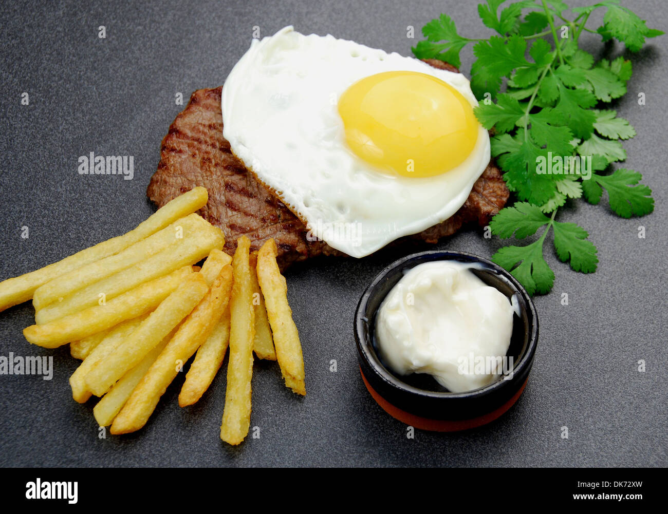 Lucky Steak. Sandwich rump steak topped with a range free fried egg, a side of French fries and mayo. - Stock Image