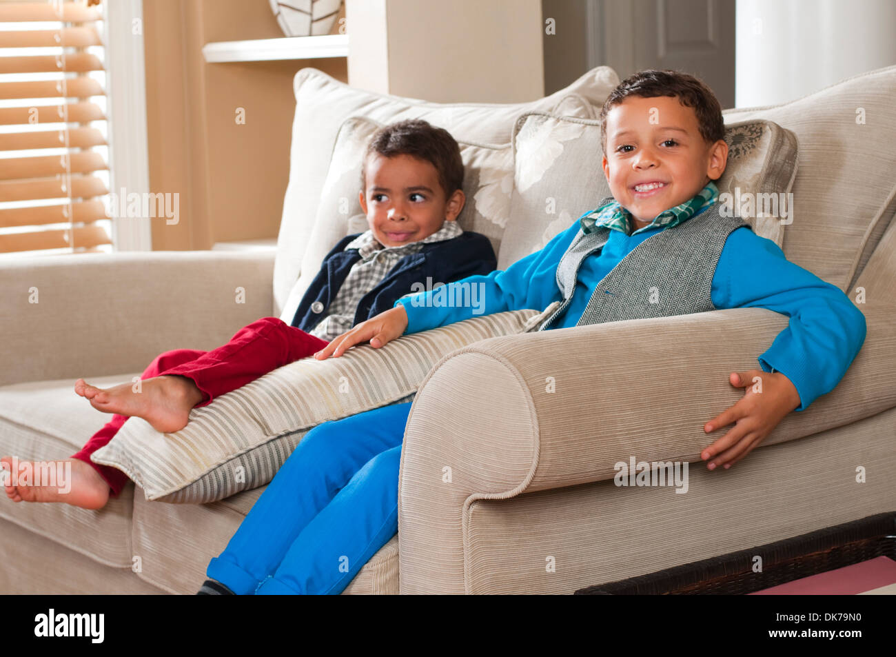 Two boys sitting on a sofa in a living room setting Stock Photo ...
