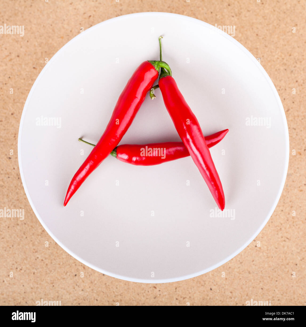 Fresh raw red hot chili peppers on plate arranged in A letter shape. - Stock Image