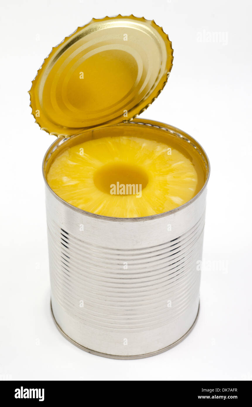 Portion of canned sliced Pineapple in a tin isolated on white background - Stock Image