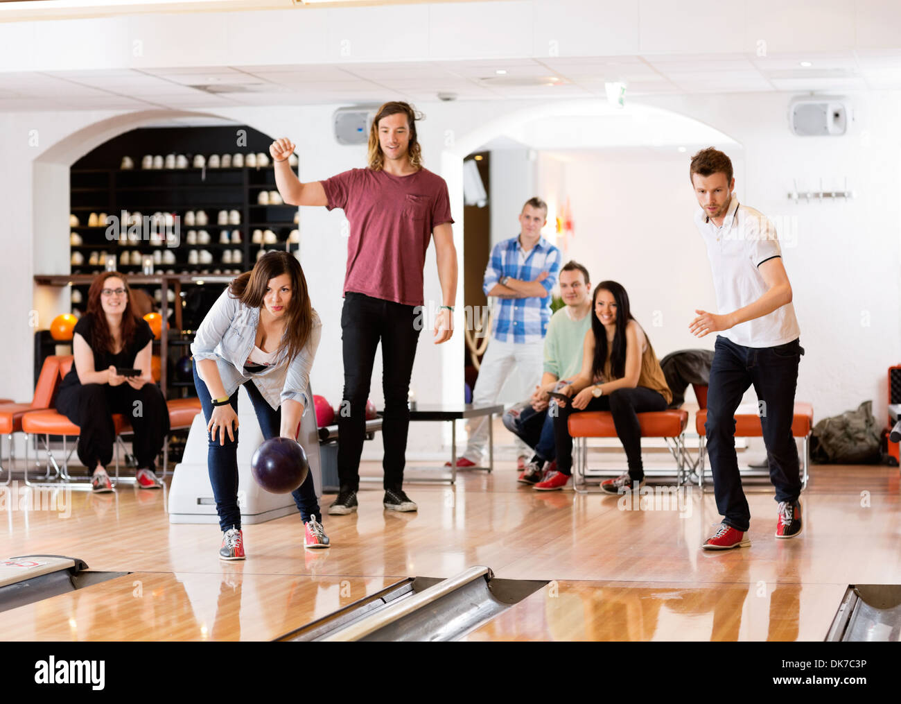Man And Woman Bowling With Friends in Background - Stock Image