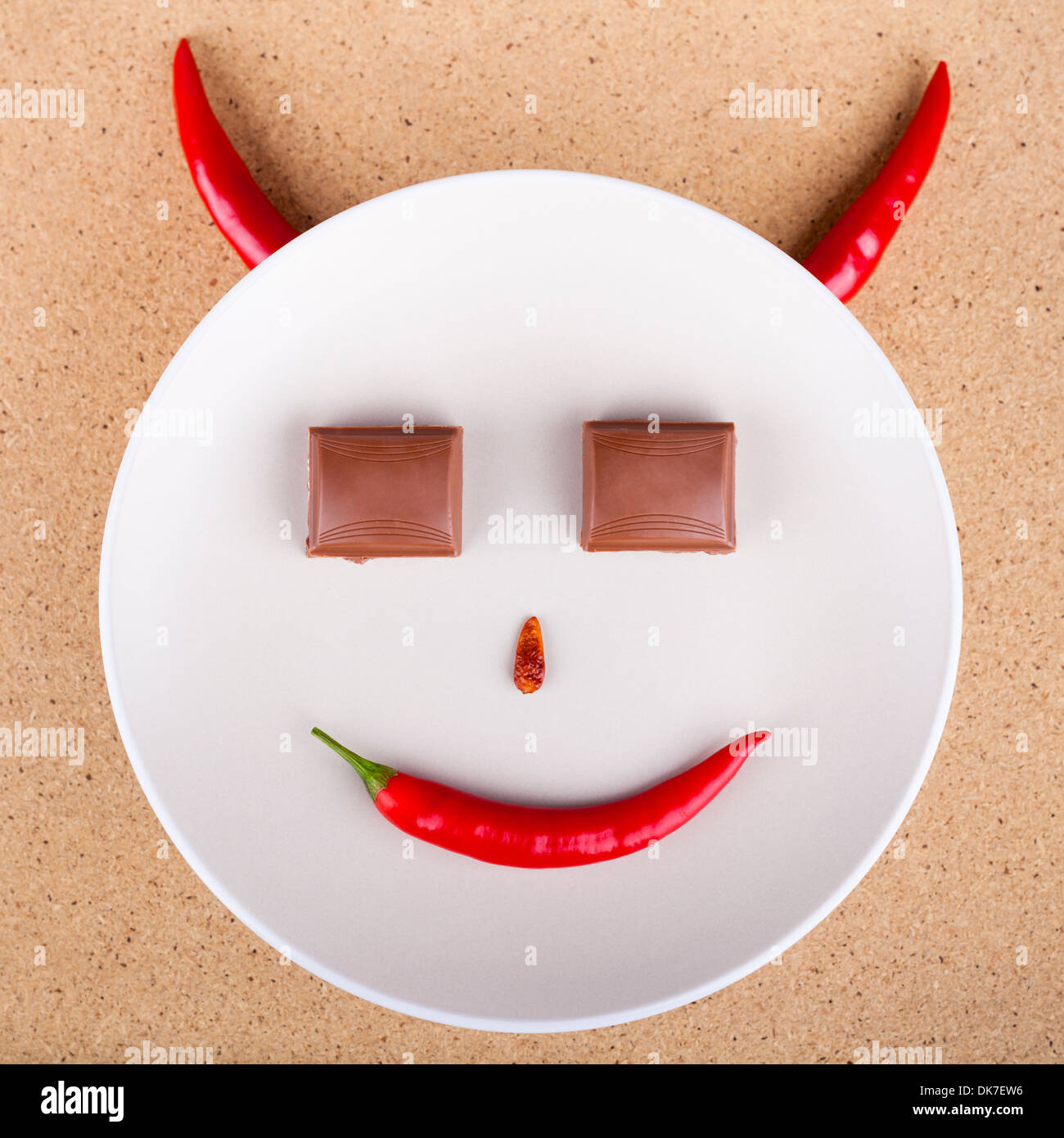 Chili pepper smiling face with chocolate eyes on plate, over wooden background. - Stock Image