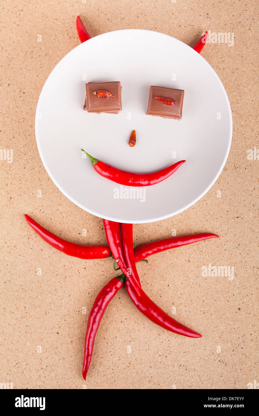 Happy chili pepper character with chocolate eyes on plate, over wooden background. - Stock Image