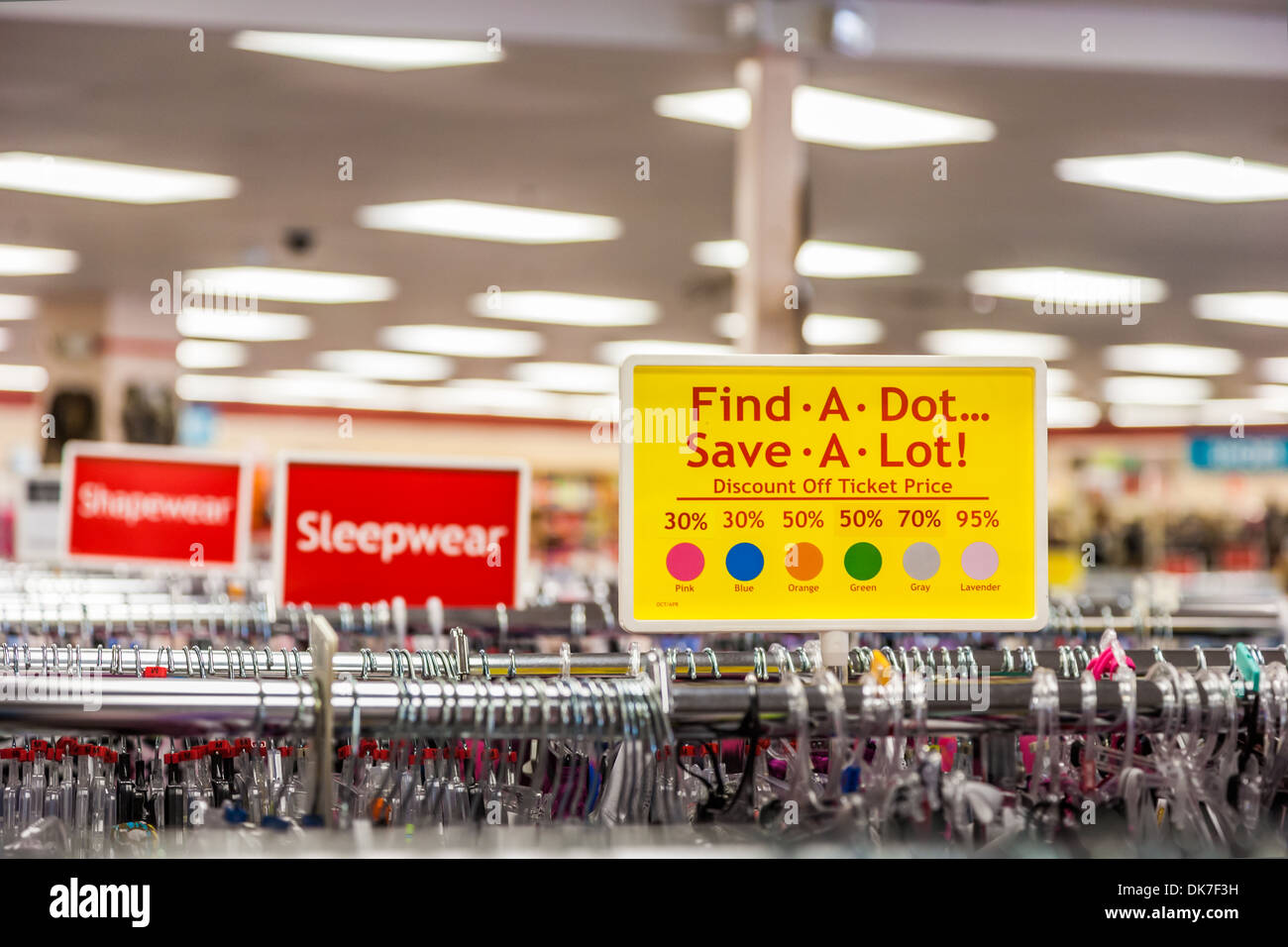 Sign indicates discounts on clothing in retail clothing bargain store - Stock Image