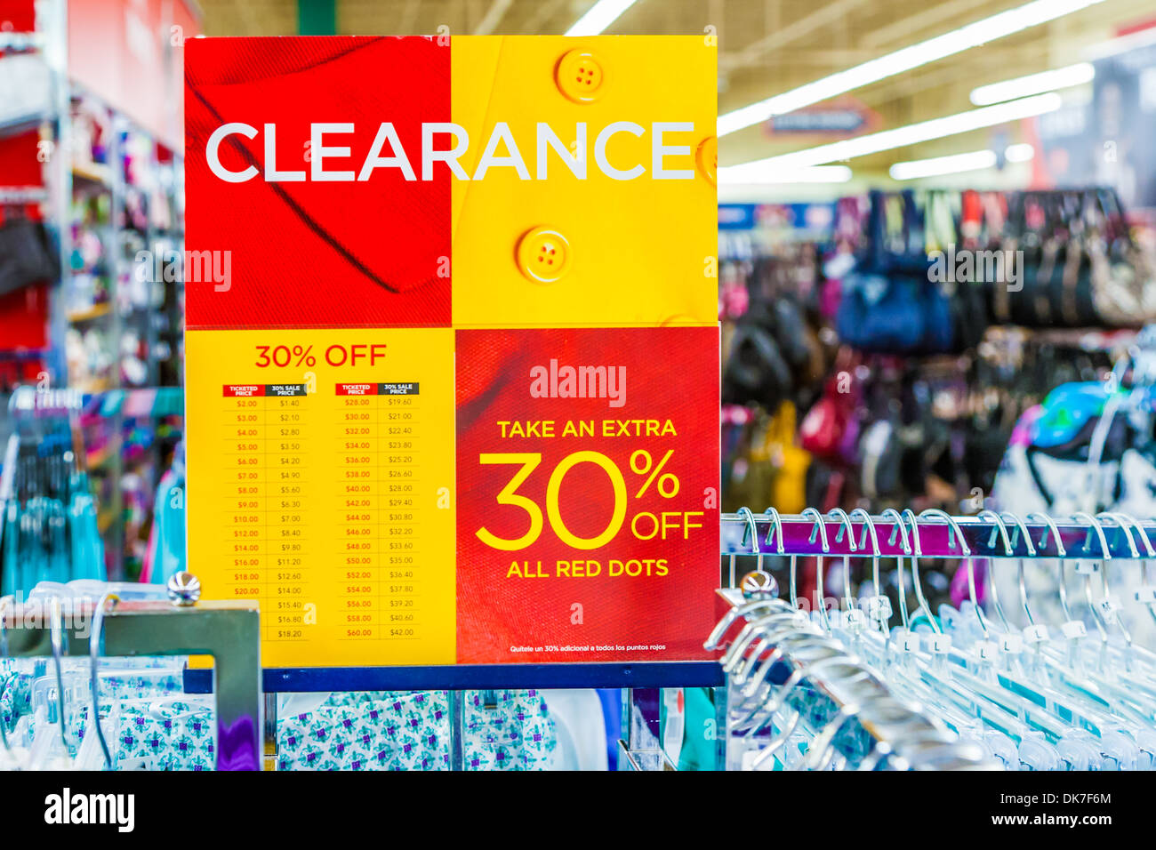 Sign indicates clearance sale discounts on clothing in retail clothing bargain store - Stock Image