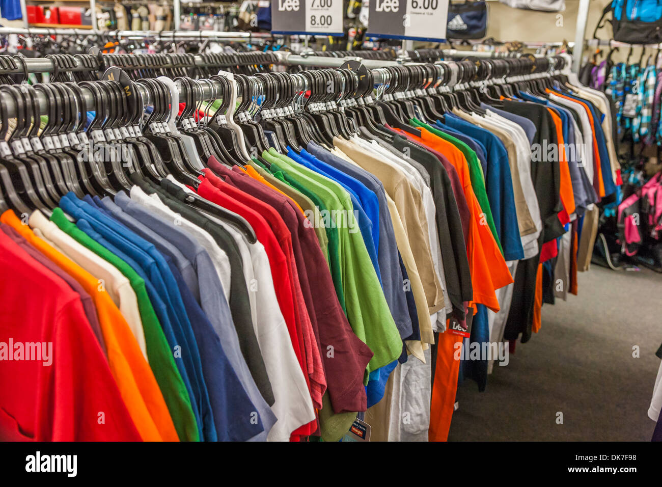 28e567bd0e84 T-shirts of all colors hanging on rack in retail discount clothing store