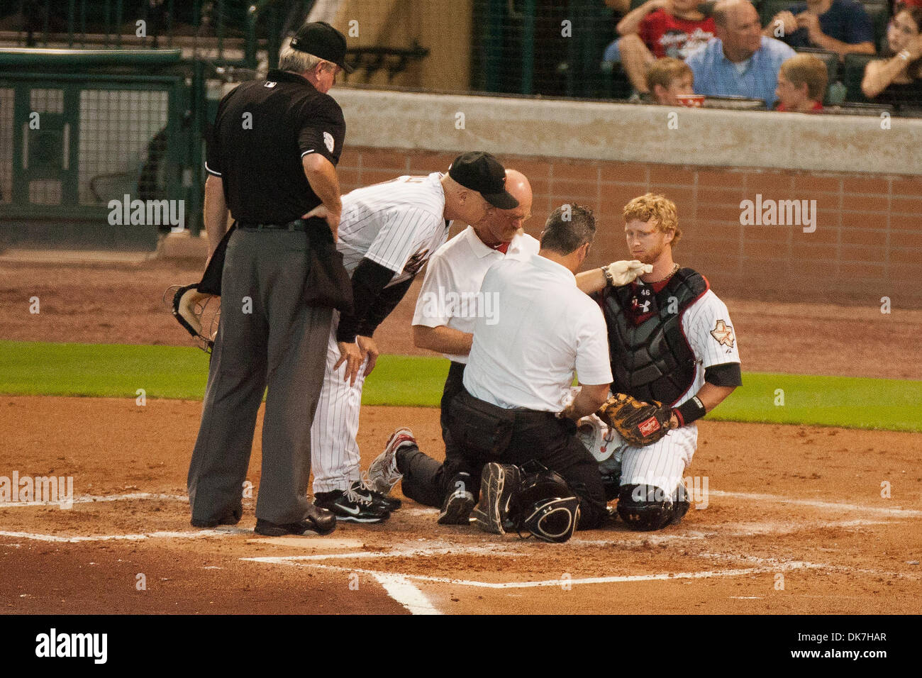 June 24, 2011 - Houston, Texas, U.S - Houston Astros Catcher J.R. Towles (46) is being looked at by Houston Astros Manager Brad Mills (2), Astros Trainers, and Home-plate Umpire Brian Gorman. Towles left the game in the top of the 3rd inning with chin lacerations, he received 11 stitches in his chin. Tampa Bay Rays beat the Houston Astros 5 - 1 at Minute Maid Park in Houston Texas. - Stock Image