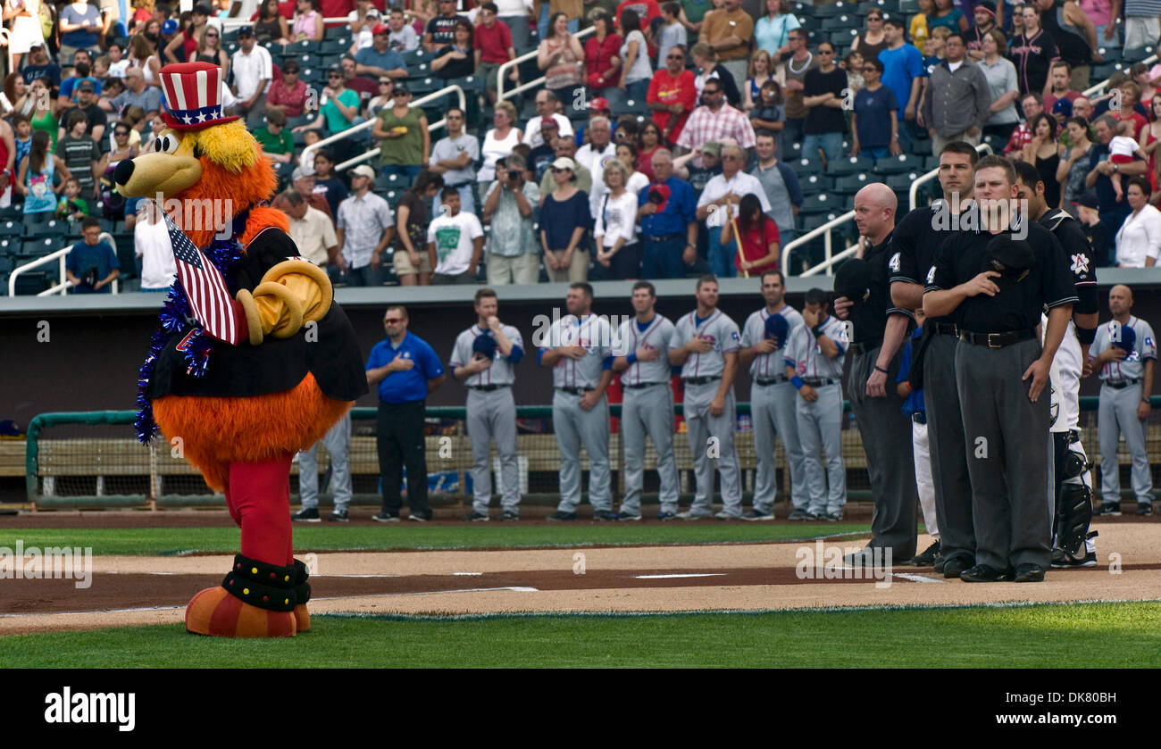 July 04, 2011 - Albuquerque, New Mexico, USA -  The Albuquerque Isotopes mascot, Orbit, the umpires, the visiting team and fans stand during the national anthem prior to the Independence Day game between the Isotopes and the Round Rock (TX) Express.  The Isotopes and the Express are the Triple-A affiliates of the Los Angeles Dodgers and Texas Rangers, respectively.(Credit Image: ©  - Stock Image