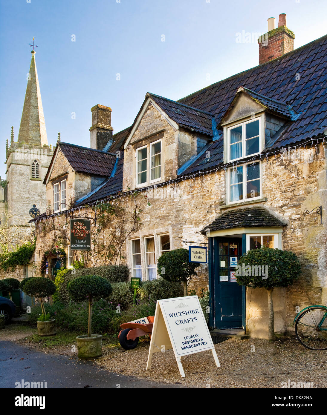Craft shop and tea rooms in the historic Wiltshire village of Lacock with the spire of St.Cyriac's church behind. - Stock Image