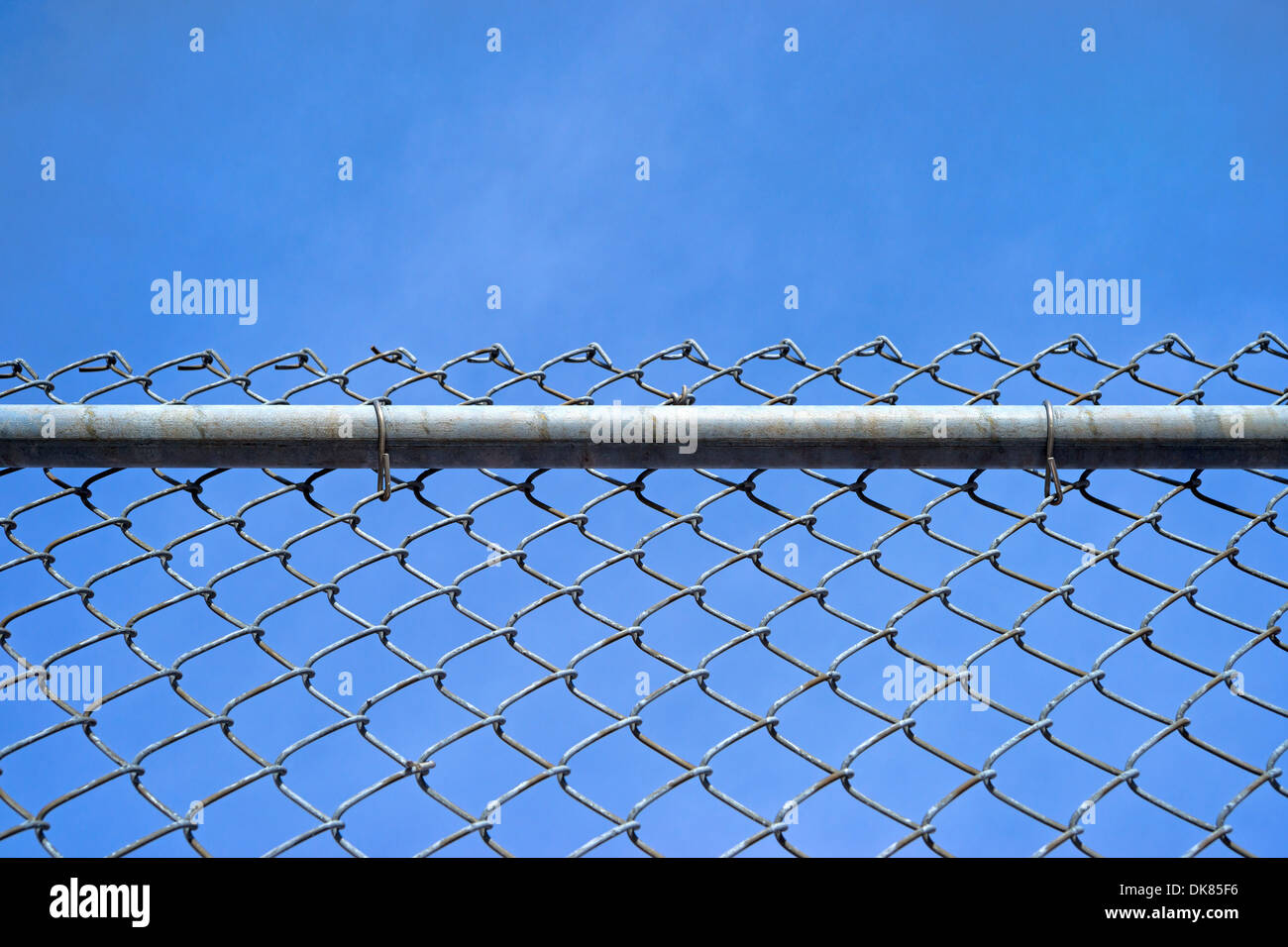 A chain link fence with a sturdy bar and fastenings against a blue sky with wispy clouds. - Stock Image